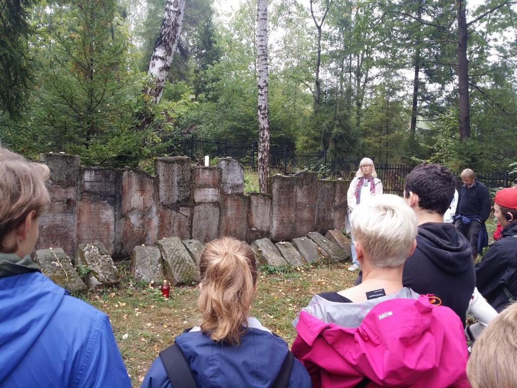 Ewa Andersson guidar elever och lärare från Norrköping på den lilla orten Rabka i södra Polen. Här upprättade den nazistiska regimen en SD-skola (Sicherheitsdienst) där soldater bland annat övade skytte på levande mål, dvs. judar från trakten. På bilden har gruppen stannat vid en symbolisk judisk begravningsplats. Gravstenarna användes av nazisterna bland annat för att bygga vägar. Foto Mathan Ravid.
